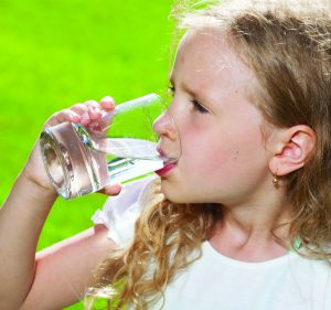 A girl practicing healthy nutrition for kids by drinking a glass of water