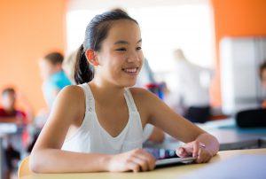 Fille assise à son bureau à l'école en regardant son bulletin