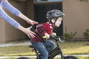 Little boy learning to ride a bike after his parents got tips from a physiotherapist.