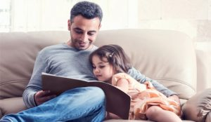Child and father reading together after seeing a Speech Language Pathologist