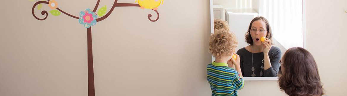 Young boy practicing speech with speech-language pathologist.