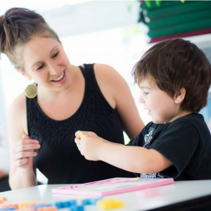 A woman happily working with a child in one of the careers available with Children Support Solutions
